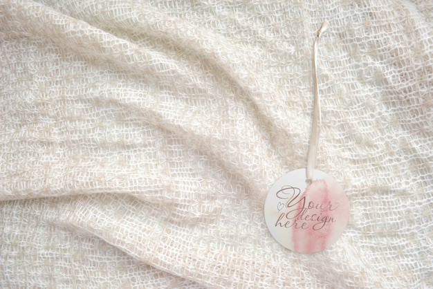 Round tag on the on a knitted light background Premium Psd