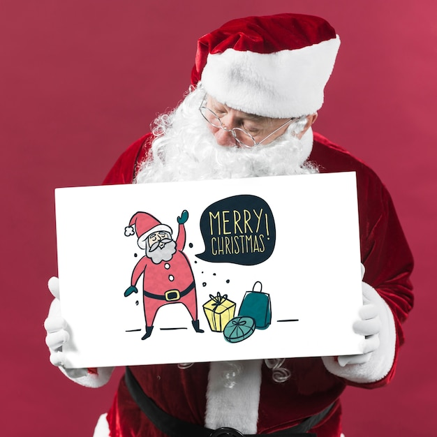 Santa presenting paper board mockup Free Psd