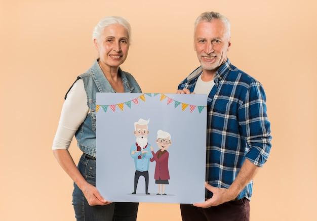 Senior couple presenting board for grandparents day Free Psd