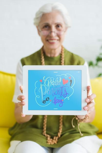 Старший женщина, держащая планшетный макет Бесплатные Psd