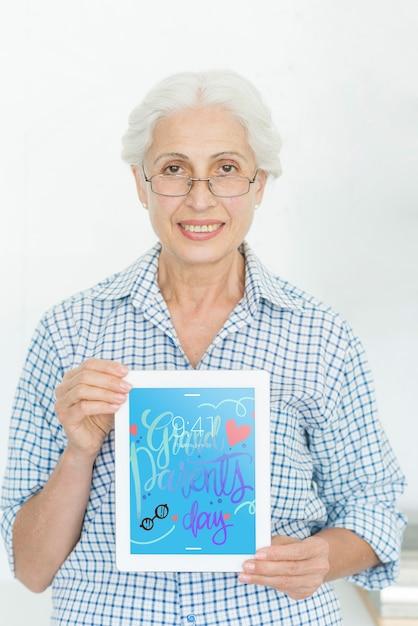 Старший женщина, держащая планшетный макет Premium Psd