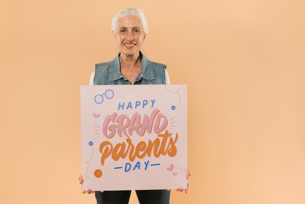 Senior woman presenting board for grandparents day Free Psd