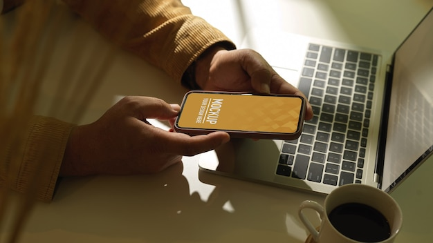 Side view of male hand holding smartphone on workspace with laptop and coffee cup Premium Psd