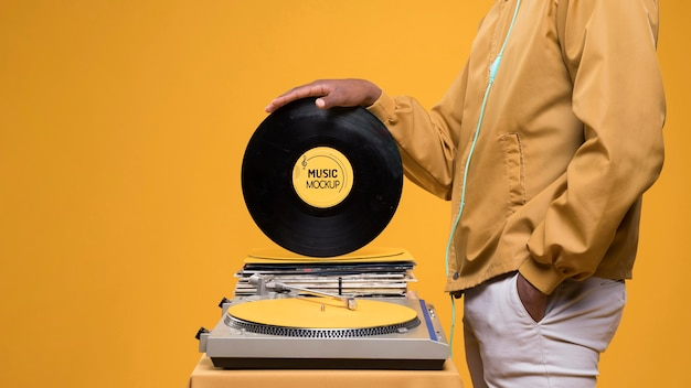 Side view of man holding vinyl disk for music store mock-up Free Psd