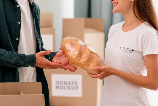 男性にパンを配る女性ボランティアの側面図 無料 Psd