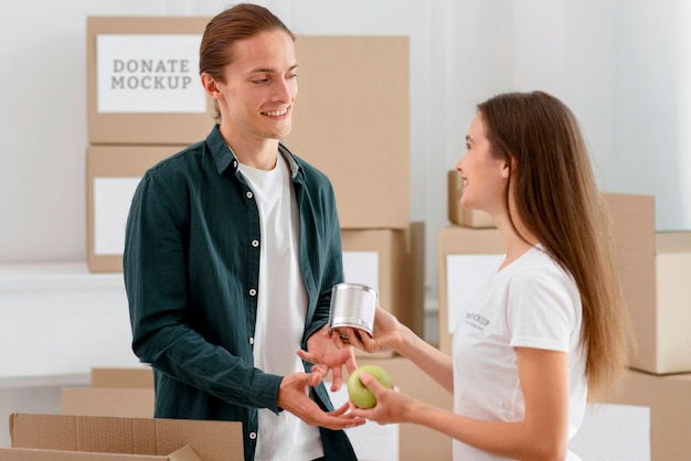 男性に食料を配る女性ボランティアの側面図 無料 Psd