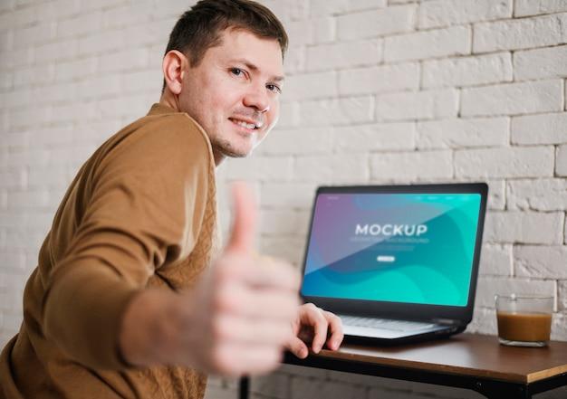 Вид сбоку человека, давая пальцы во время работы из дома Бесплатные Psd