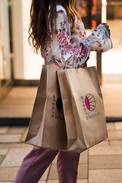 Donna di vista laterale che tiene i sacchetti della spesa Psd Gratuite