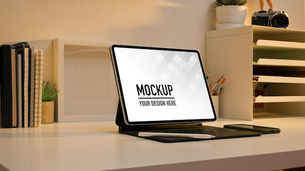 Side view of worktable with digital tablet mockup and supplies in home office room Premium Psd