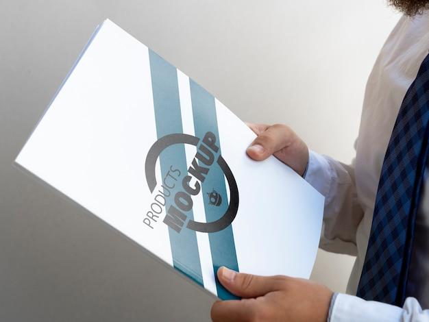Sideways man holding a notebook mock-up Free Psd