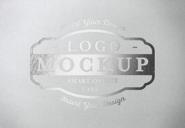 Silver pressed logo mockup on white paper texture Premium Psd