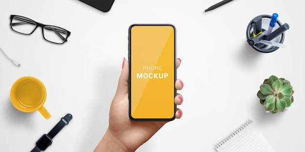 Smart phone in woman hand mockup, above work desk. top view, flat lay composition Premium Psd