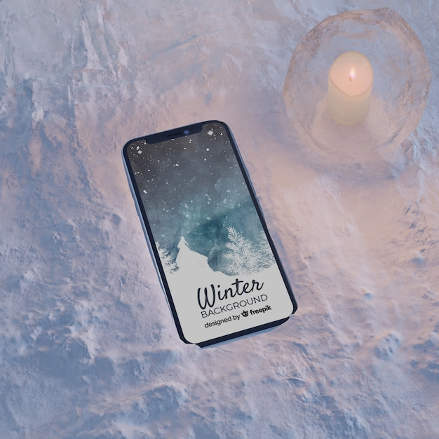 Smartphone on ice block light by candle Free Psd