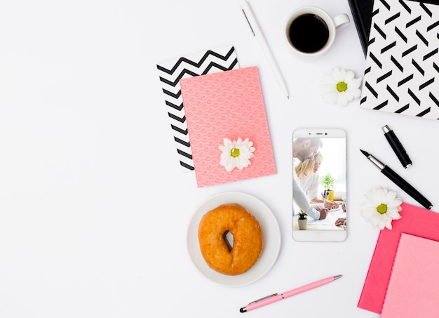 Smartphone mockup with breakfast in office Free Psd