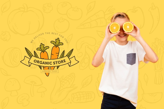 Smiley child posing with oranges over eyes Free Psd