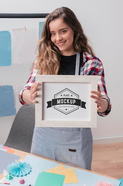 Smiley female artist holding mock-up frame Free Psd