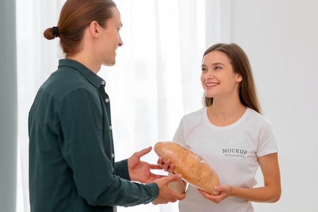 Смайлик женщина-волонтер раздает хлеб мужчине Бесплатные Psd