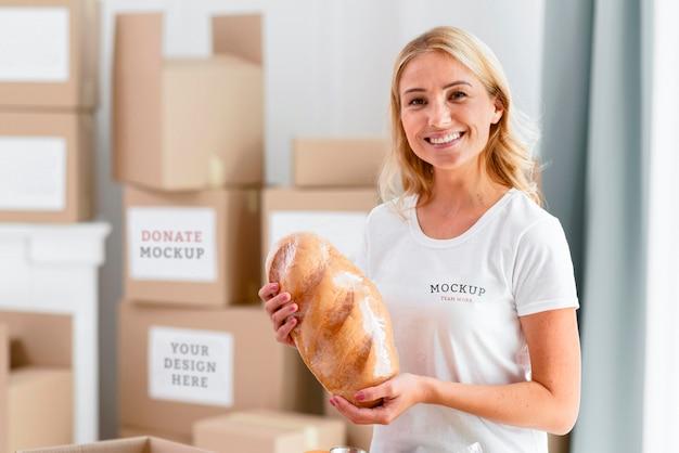 Смайлик-волонтер женщина держит хлеб для пожертвования Premium Psd