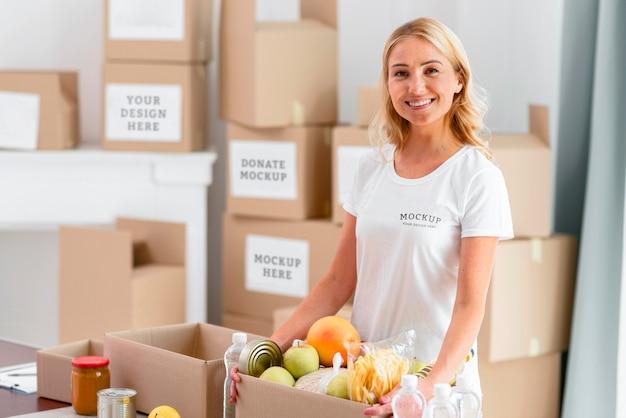 Смайлик-волонтер держит коробку для пожертвований с едой Premium Psd