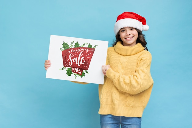 Smiley girl holding paper sheet with sales message Free Psd