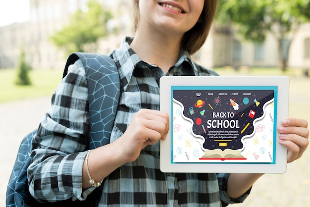 Smiley girl holding a tablet mock-up Free Psd