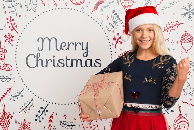 Smiley girl with santa hat holding gift Free Psd