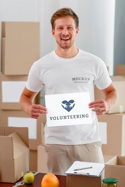 Volontario maschio di smiley che tiene carta bianca con scatole di cibo per la donazione Psd Gratuite