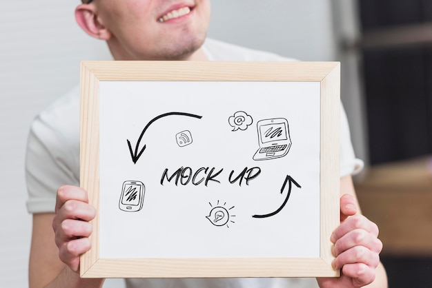Smiley man holding mock-up frame Free Psd