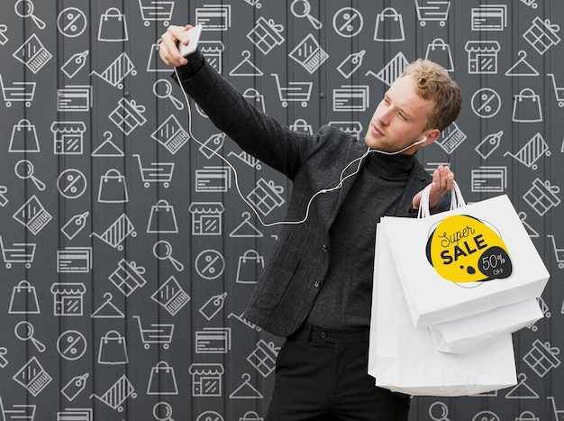 Smiley man taking selfie with his shoppings Free Psd