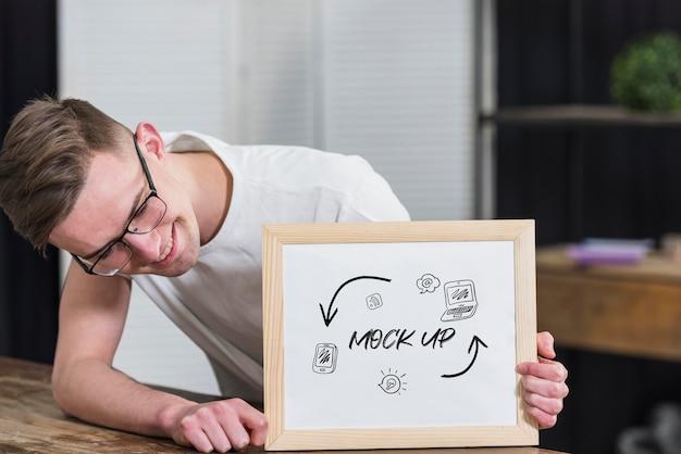 Uomo sorridente con gli occhiali che tiene il telaio mock-up Psd Gratuite