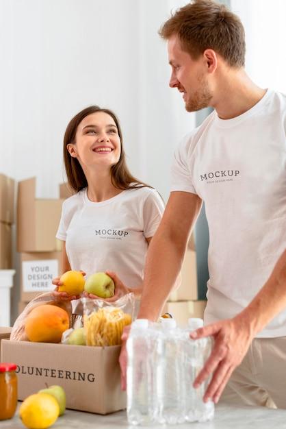 Волонтеры smiley готовят ящики с продуктами для пожертвований Бесплатные Psd