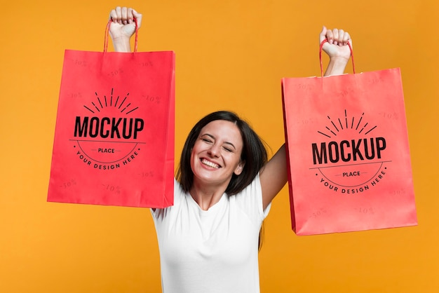 Smiley woman holding shopping bags mock-up Free Psd