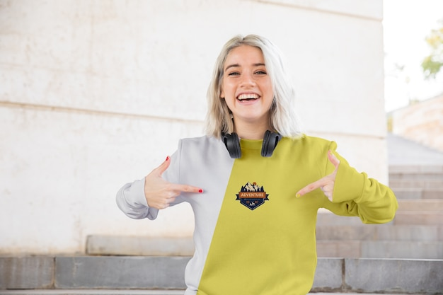 Smiley woman pointing at hoodie Free Psd