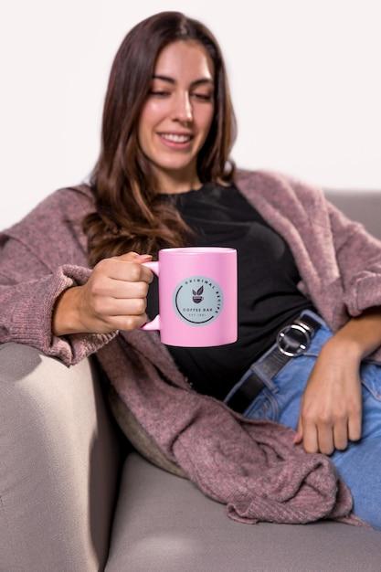 ソファに座ってマグカップを持つスマイリー女性 無料 Psd