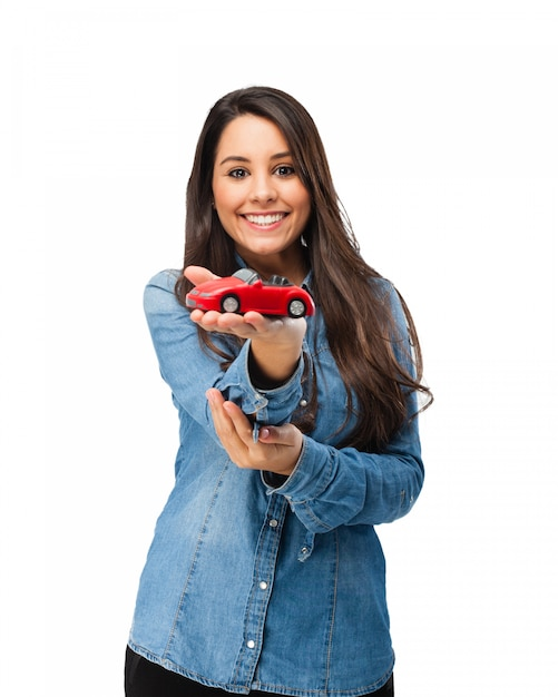 Smiling girl showing the car of her dreams Free Psd