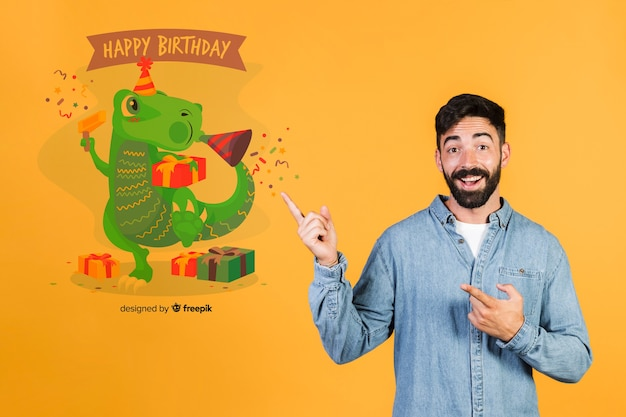 Smiling man pointing fingers to a happy birthday message Free Psd