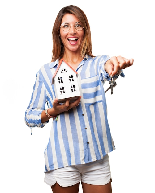 Smiling woman holding keys and toy house Free Psd