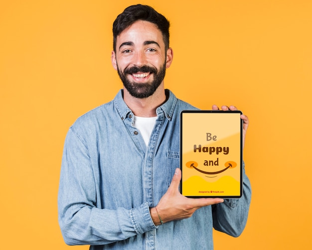 Smiling young man holding tablet mock up Free Psd