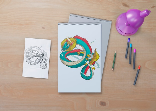 Snake sketch on white sheets on table Free Psd