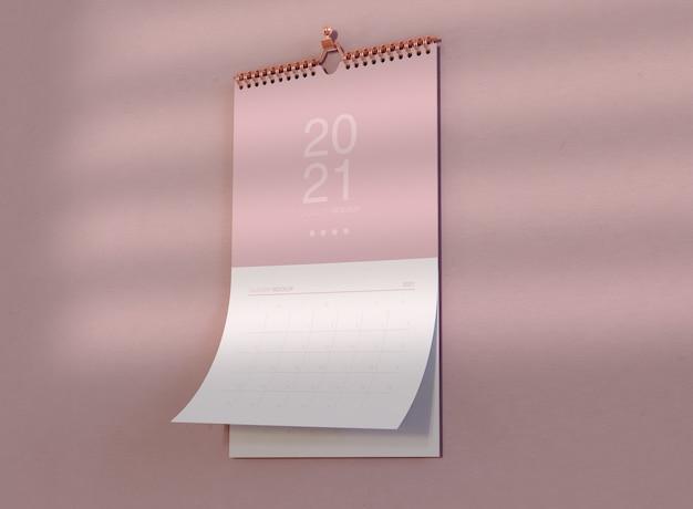 Мокап спирального календаря, висящий на стене Premium Psd