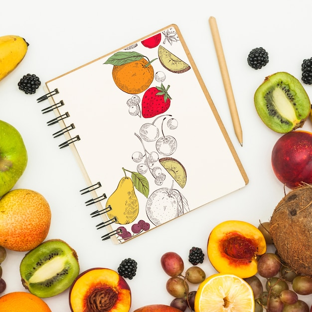 Spiral notebook mockup with fruits Free Psd