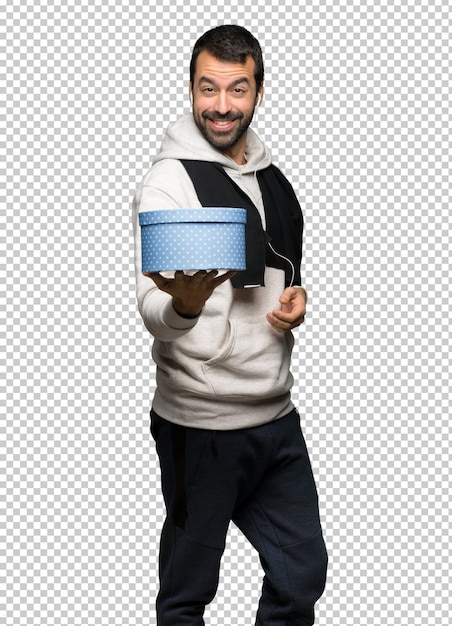 Sport man holding a gift in hands Premium Psd