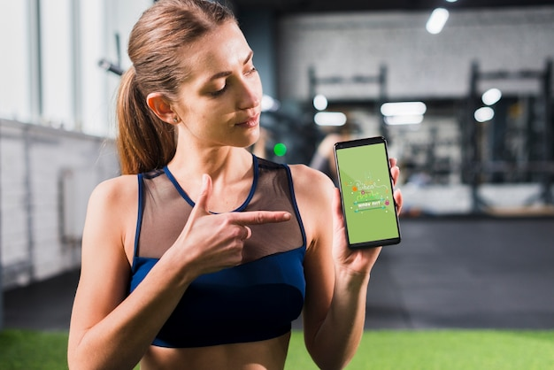 Sporty woman pointing at smartphone mockup Free Psd