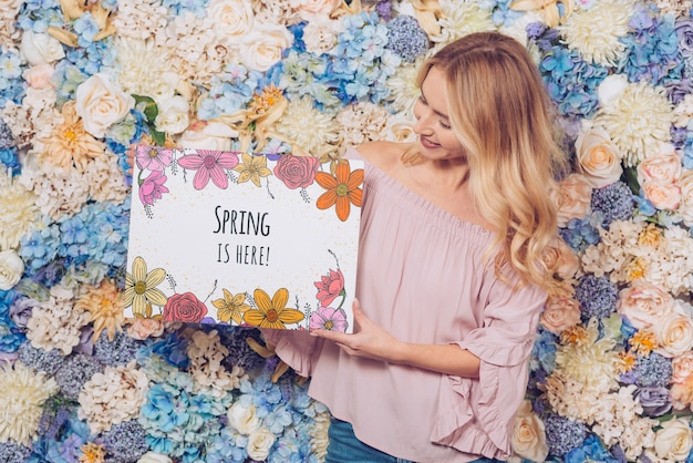 Spring concept with woman holding paper mockup Free Psd
