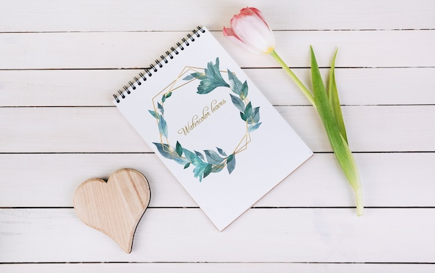 Spring notebook mockup with decorative plant in top view Free Psd