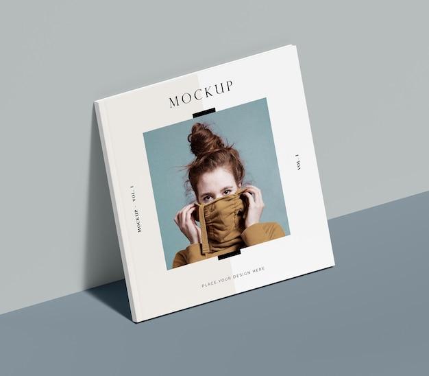 Libro quadrato con mock-up rivista editoriale donna appoggiata al muro Psd Gratuite