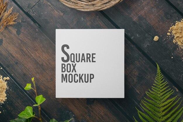 Дизайн макета квадратной коробки на деревянном столе Premium Psd