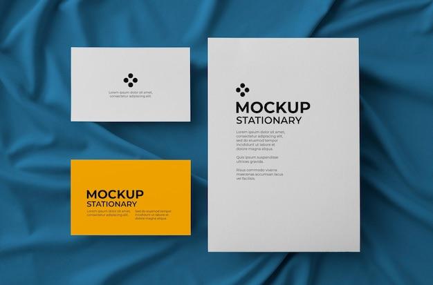 패브릭 배경 모형 위에 큰 카드와 두 개의 비즈니스 카드가있는 고정식 무료 PSD 파일