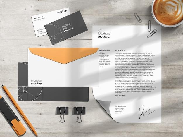 レターヘッド、名刺、封筒を作業机の上に置いた文房具ブランディングアイデンティティモックアップテンプレートとシーンクリエーター Premium Psd