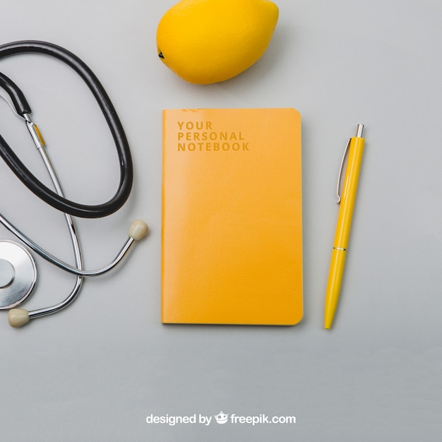 Stethoscope, lemmon, notebook and pen Free Psd